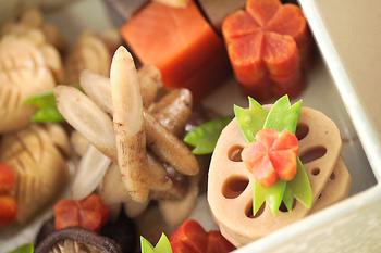 """縁起の良い野菜をたくさん入れて、よく味をしみ込ませたお煮しめは、各家庭で伝えていきたい一品ですね。  地中深くまでまっすぐ長く根を張る「ゴボウ」は、長生きの象徴として。縁起の良い朱色の「にんじん」、たくさん穴がある「レンコン」は、見通しが良いという意味があります。そして運が良くなるという意味を込めて""""ん""""がついた食材を入れ運気アップ!飾り切りをあしらえば、より華やかに。"""