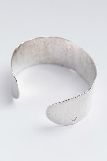 シンプルながら存在感のあるPercheのシルバーバングル。なめらかな槌目は温もりがあって、太めのシルエットは手首を華奢に見せてくれますね。