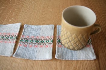 「ローゼンゴング(バラの道)」という技法で、スウェーデン製の綿麻糸を手織りしたコースターです。色褪せしにくく、へたりにくいので、汚れを気にせず毎日のティータイムに使ってもらいたいですね。温かみのある柄と風合いが、寒い季節をほっこりさせてくれます。