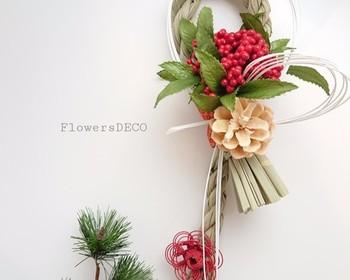 光沢のある赤い実と緑の葉っぱのコントラストが美しい「万両」と松ぼっくりを使った、パッと華やかなしめ縄。万両はたくさんの実をつけることから、慶祝や財産など縁起の良い花言葉をもっているんですよ。
