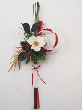 縦長シルエットがステキお正月飾り。椿、松、シダ、千両、稲穂、水引などお正月にゆかりのあるアイテムをシンプルにまとめています。中央の大きな椿と紅白の水引がインパクト抜群で、玄関の内、外どちらに飾ってもステキですよ。