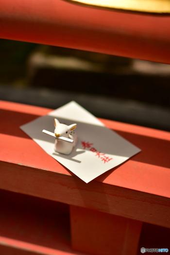 """小さな白い鹿がおみくじを口にくわえている姿が、何とも愛らしい奈良公園内にある春日大社の陶器製""""白鹿みくじ""""。おうちに持って帰って飾っておきたくなる可愛さです。(1つ600円)"""