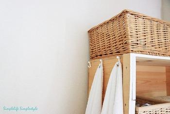 収納棚は側面をタオル掛けにも使えます。タオルハンガーを付けてもいいし、こちらはタオル中央の端っこにハドメ金具を取り付け引っ掛けられるようにした収納アイディア♪