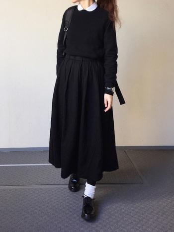ニットからちらっと覗かせたシャツの襟と、白ソックスのアクセントがとってもキュート。上下黒のシックな色合わせでも、ほんの少し白を効かせることで、女性らしさや可愛さがプラスされます。コンパクトにまとめたトップスと、ふんわりシルエットのスカートが絶妙のバランス。