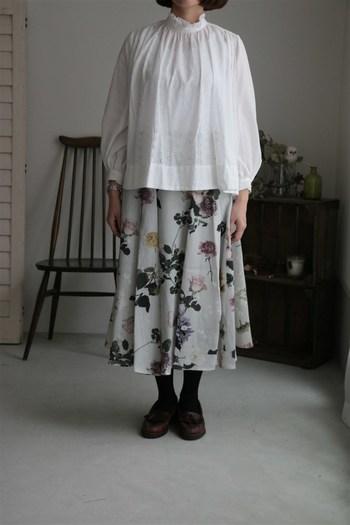 白色のブラウスに、グレートーンの花柄スカートを合わせた着こなしです。黒タイツやブラウンのシューズで季節感を出しつつ、ナチュラルなコーデに仕上げています。寒くなってきたら、無地のアウターを合わせるのがおすすめですね。