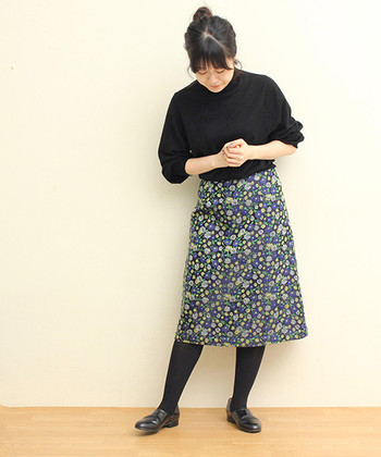 黒のニットに花柄スカートを合わせて、タイツもシューズも黒でまとめたスタイルです。花柄感の強いスカートには、同色でまとめたアイテムで合わせると大人な着こなしができますよ。