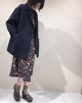 花柄のワンピースに、ネイビーのジャケットを合わせたコーデ。ワンピースとジャケットの色を合わせることで、大人かわいい着こなしに。