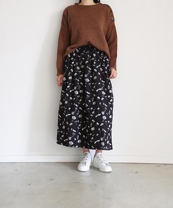 ネイビーの花柄スカートには、ブラウンのニットをボトムインした着こなしに。足元は白のスニーカーを合わせて、シックなコーデをちょっぴりラフな印象にカジュアルダウンしています。