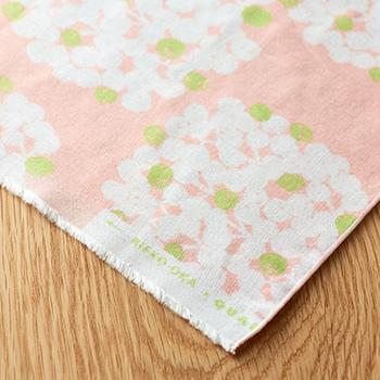 北海道在住の模様作家、岡理恵子さんデザインの「てぬぐい」。薄くて軽い40番の糸で二重に織り上げたガーゼ素材に、繊維を揉みほぐすタンブラー加工を施して、ふっくらと柔らかな風合いに仕上げました。やさしいピンクが女性らしい1枚。