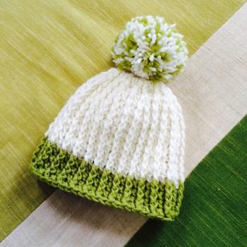 2色の毛糸で編んだ、大きなぽんぽんがかわいいニットキャップ(帽子)です。網目の数を変えるだけで、子ども~大人用まで作ることができます。親子でお揃いもいいですね。