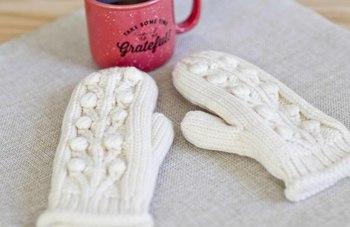 柔らかな印象の白い毛糸で編んだミトンタイプの手袋。北欧を思わせる模様のざっくりとした編み目もとても素敵です。
