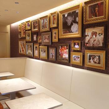 白を基調としたイートインスペース。壁にはフランス国家最高職人(MOF)の称号をもつオクシタニアルのエグゼクティブシェフ、ステファン・トレアン氏やお菓子の写真などが飾られています。