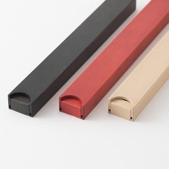 色は長手角のお弁当箱と同じく、朱・黒・白の3色展開。素材は国産ヒノキを使用しており、拭き漆の技法で美しい木目を活かし、素材そのものの風合いを楽しむことができます。箸箱はスライドさせて台とケースに分解できるので、洗いやすく衛生的に使用できるのもポイントです。