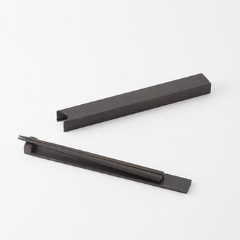 漆琳堂が手掛ける拭き漆で仕上げた箸箱は、スライド式の箸箱が箸置きに変身するというユニークなデザインが特徴です。写真のように箸箱から箸を台ごと取り出し、先端部分に箸先をのせると箸置きの完成。お弁当を食べる時に意外と困ってしまうのが「箸の置き場所」ですが、これならテーブルもお箸も汚さず、快適なランチタイムが過ごせそうですね。