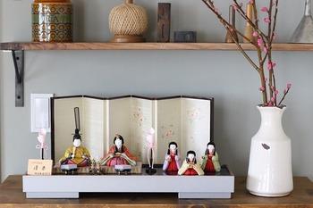ひなまつりにかかせない雛人形は、小さなものが場所を取らずに飾れて◎。桃も一緒に飾っておくと、素敵ですね。