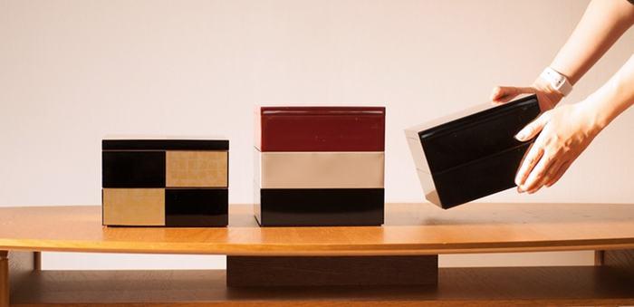 日本デザインストアのオリジナル重箱は、現代の食卓にマッチするモダンなカラーがとってもおしゃれ。旅館や料亭の漆器を手掛ける越前漆器の老舗工房に特注し、職人さんが一つ一つ丁寧に仕上げた逸品です。重箱のカラーは「深紅・鈍色・漆黒・金煌・銀煌」の5色に加えて、フレンチシックを思わせるおしゃれな3色セットを展開。サイズは6.5寸(約19.5㎝)の大と、4.5寸(約13.5㎝)の小の2種類から選ぶことができます。