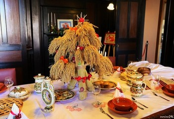 """ウクライナではグレゴリオ暦の1月7日がクリスマス。イブの夜には家族全員で12種の伝統料理が並ぶ食卓を囲みます。 テーブルの中央に置かれた藁の馬には、""""家族も家畜も一緒に祝う""""という意味が込められています。クロスの下にも藁を置き、引いた藁の長さによって来年の運勢を占うそう。"""