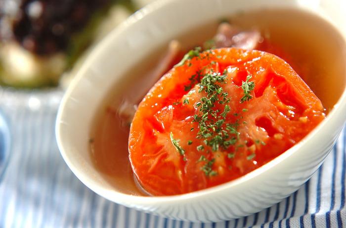 目も楽しませてくれる、丸ごとトマトのスープです。サラダ油を入れて熱した鍋でまずベーコンを炒め、香りを立たせます。そこに味付けしたスープの材料を加え、煮たつのを待って半分に切ったトマトをそのまま入れます。再び沸騰したら塩コショウでお好みの味に仕上げます。ドライパセリを散らして飾ったら、崩しながら召し上がれ♪