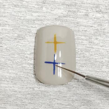 ①お好みのベースカラーを塗り、真ん中に縦2つ、十字を描きます。ベースカラーはベージュなど馴染みやすい色を使用することで、柄に色を使っても派手になりすぎず、上品なアーガイルを楽しめます♫