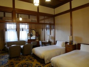 本館デラックスルームはベッドルームとラウンジエリアが暖簾で仕切られており、その先には豪華な応接セットと鏡台、書き物ができるデスクが。ベッドタイプの洋室ですが和のムードが漂い、海外からのお客様からの評判が高いのも納得です。