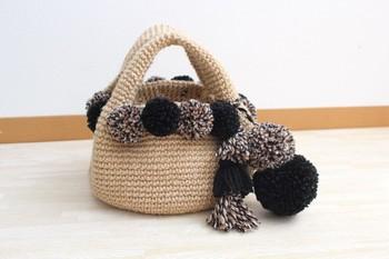 シンプルなバッグにポンポンをたくさんあしらって。ポンポンの色合いがシックなので、たくさんつけても落ち着いた雰囲気があります。さりげないぬくもりが感じられるバッグですね。