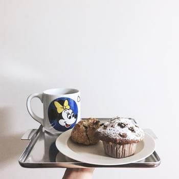 kaeさんが使っているアルミのトレーや乳白色のシンプルなプレートはイイホシユミコさんのもの。ボリュームたっぷりな埼玉県戸田市にある「まめしばコーヒー」のシュトレンマフィンと、埼玉県川口市にある「センキヤ菓子店」のスコーンを乗せて。ミニーマウスのマグカップがレトロでキッチュなイメージに。