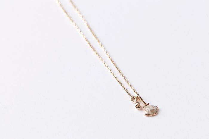 子のネックレスの魅力はシェルを混ぜた樹脂デザインの面と、シェルのプレート面とのリバーシブルで楽しむことができる点。