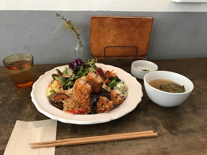 お食事メニューは「有機玄米おばんざいプレート」のみ。主菜は「豆腐ハンバーグ(肉不使用)」「全粒粉の車麩フライ」「玄米塩麹漬け鶏の唐揚げ」の3つと、「本日のおすすめ」の日替わりが数種類。その中からをひとつ選びます。写真は衣がサクサク、中はモチモチの食感も楽しい車麩フライ。