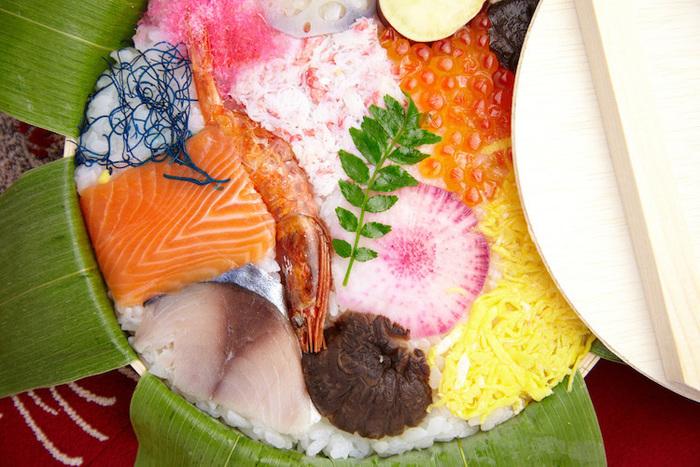 金沢のハレの日の伝統料理「金澤寿し」は、笹を敷いた丸い曲げわっぱに、フグの糠漬けや干し甘えびなどを並べた押寿しです。乾燥海藻を青色に色づけた「紺のり」も入っていて、とてもカラフルですね。この押寿し作りを体験できるところもあるので、金沢を訪れた際には自分で作ってみるのもいいかもしれませんね。