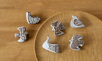 こちらは「BIRD'S WORDS(バーズワーズ)」の鳥たちのブローチ。模様によって生まれた凸凹で、釉薬のかかった部分と、うっすら土の色が透ける部分とが組み合わさり、やわらかな風合いをもたらしています。こちらは6種のトリが愛らしい表情を見せる「bird tile」シリーズ。