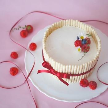 生クリームを塗ったスポンジの周りにポッキーを並べ、シャルロット風に仕上げたケーキ。生クリームの色に合わせて、ポッキーはレモンクリームをベースにした「カラフルシャワー」が使われています。白で統一され、おしゃれながらもインパクトのあるホールケーキです。