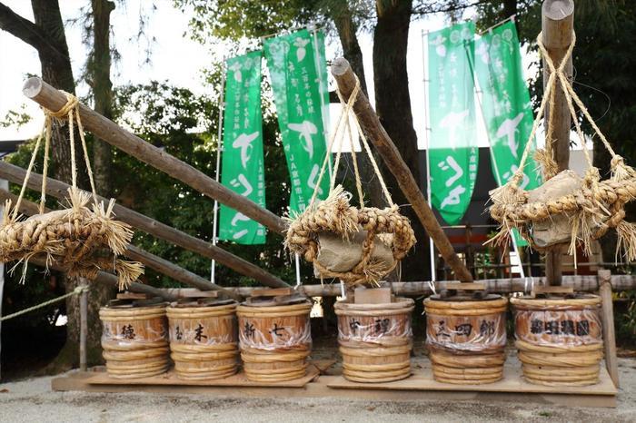 """すぐきに使われる酸茎菜(酸茎蕪)は、京都伝統野菜の一つで、かぶの変種。 この野菜は、上賀茂の社家(しゃけ/世襲で続く神職家のこと)から始まり、かつては上賀茂周辺のごく限られた地域のみで栽培され続けてきたものです。現在では京都を代表する漬物になりましたが、江戸期までは上層階級のみが口に出来た高級品だったと云われています。  「すぐき漬」は、「すぐき」の根本や皮などを削ぎ取りした後、一旦塩で荒漬けし、その後""""てこ""""の原理を利用した""""天秤押し""""という方法で、圧力をかけて本漬けし、乳酸発酵させ、熟成させます。  【画像は、上賀茂神社「武射神事」に奉納された「すぐき漬け」。重い石を天秤棒の先にぶら下げ、漬け樽に圧力をかけて、本漬けしています。】"""