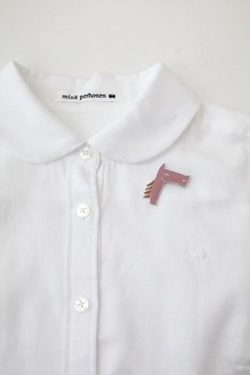 「mina perhonen」のサラブレッドブローチ。一度見たら忘れられないユニークな表情と、甘すぎないシャープなデザインが印象的です。ピンクとブラウンの2色から、お好みのものを選べます。