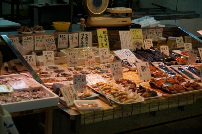 """【清流が幾筋も流れ、琵琶湖も近い京都では、古くから""""魚""""といえば、淡水魚。鮎や鯉、鮒や諸魚(モロコ)等の淡水魚を、甘露煮や熟れ寿司等にして保存食にしてきました。現在でも「錦」には、そうした淡水魚だけを商う専門店があり、地元で親しまれています。  (画像は、「のとよ西店」の店頭。「のとよ」は、錦に二店舗あり、「味彩 のと与」とでは、うなぎ丼や川魚料理がリーズナブルに頂ける。「西店」では、鮮魚の他、鯉こくや天ぷら、佃煮等、川魚の惣菜が多彩に並んでいます。) 】"""