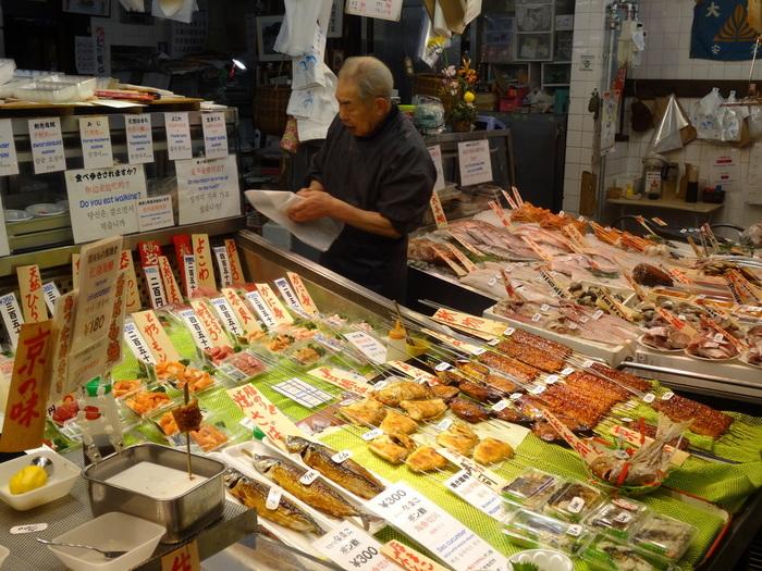 【先に紹介した『魚串』の「木村鮮魚店」店頭。食べ歩き用の商品は、ごく一部。店先には、日本海や瀬戸内海などで水揚げされた旬の鮮魚や刺し盛り、焼き魚等が種類豊富に並べられ、地元客やプロの調理人のための商いがなされています。】