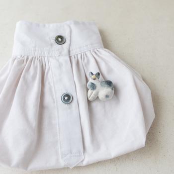 存在感のある立体的な猫ブローチ。日本の伝統工芸である、土人形のブローチです。丸みのある柔らかなフォルムと、ユニークな表情が魅力的。シンプルなアイテムのアクセントにぴったりですね。