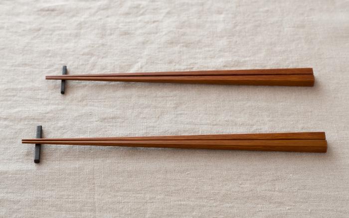 『竹箸 拭き漆 燻し煤竹』  竹のしなやかな強さを活かした細い箸。「燻し煤竹」とは、古い建築などの材で用いられ、囲炉裏の上などで長く燻された竹のこと。竹の素材を感じながらも、洗練された凛とした佇まいがどこかスタイリッシュな印象です。