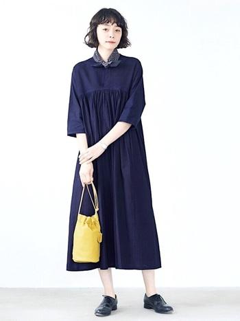 イエローの巾着バッグが、シンプルなモノトーンファッションのきれいなさし色に。明るくきれいな色合いが素敵。