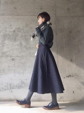 チェックのストールに、紳士風のレザーシューズ。品行方正な小物たちで脇役を固めれば、キルティングスカートもトラディショナルな趣にシフトします。