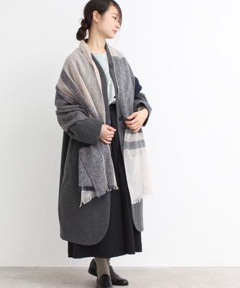 コートの色味に合わせたパターンカラーのストールがおしゃれ。落ち着いた印象ながらもセンスのよさが光ります。