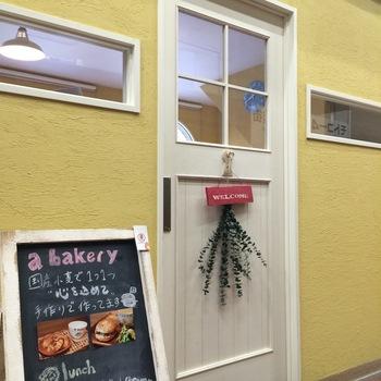 元町の高架下にある「エー ベーカリー(a-bakery)」は、手作り、国産小麦にこだわった手作りのベーグルが楽しめるお店。からしいろの壁に白い扉がかわいいですね。まるでおしゃれな雑貨屋さんに来たみたい。