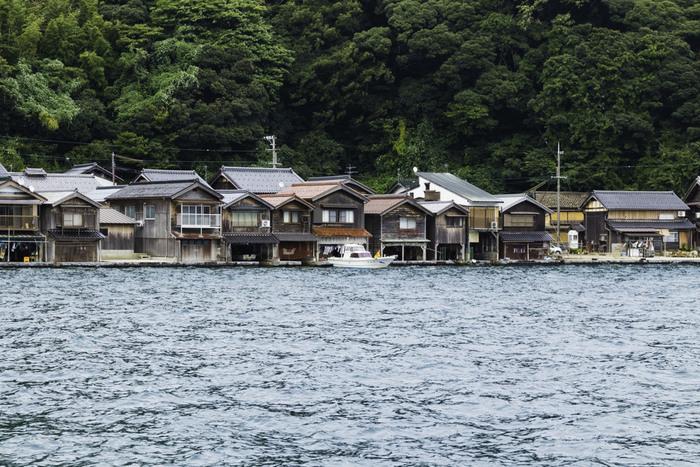 伊根町には、「舟屋」と呼ばれる1階部分が船のガレージ、2階部分が居住部分となっている独特の家屋が軒を連ねています。舟屋は、海辺ギリギリに建てられているため、遠望すると、まるで家が海の上に浮いているかのように見えます。