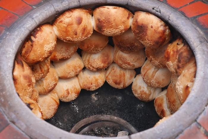 胡椒餅(フージャオピン)は炭火の釜の側面に貼り付けて焼く、パン生地っぽい中華饅頭。夜市で連日行列ができるほど熱狂的ファンが多い一品で、台湾B級グルメの代表格と言えるでしょう。釜を開けた瞬間に広がる、香ばしい匂いがたまりません。