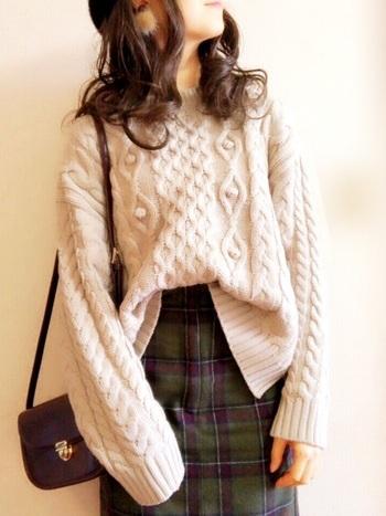 まずは気軽に取り入れやすい、ホワイトニットを取り入れたコーデからご紹介します。  飽きのこないケーブル模様のホワイトセーターと、タータンチェックのグリーンのスカートを合わせて、オシャレだけど温かみのあるスタイルに。
