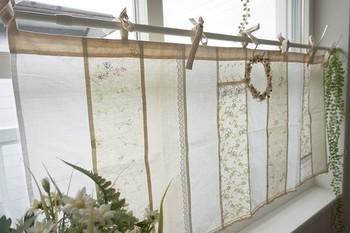カフェカーテンにひもを縫って、突っ張り棒に結んで使うタイプのカフェカーテン。ナチュラルな雰囲気の生地を組み合わせたパッチワークが素敵。S字フックでさりげなくミニリースや植物を吊るすのも◎