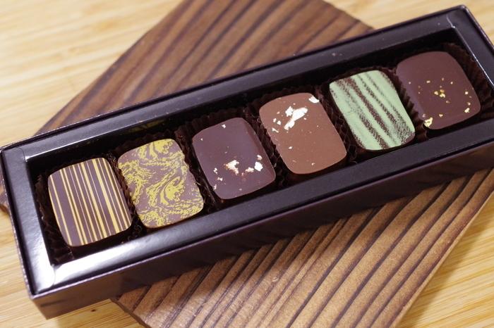 日本人ショコラティエだからこそと評判なのが「利き酒ショコラ」です。三枝氏が、東日本大震災後に宮城県を訪れ、復興に向けて力強く歩まれる宮城の酒蔵の方たちと出会ったことがきっかけで生まれたショコラ。  宮城の日本酒を使ったお菓子やショコラを作ることによって、その素材を多くの方に知っていただきたい…という想いで作られたそう。日本酒の香りとカカオの風味のマリアージュを一粒一粒に感じます。