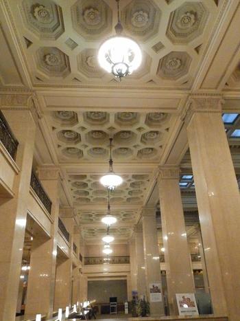 明治生命館は、昭和の建造物として初めて重要文化財の指定を受けたことでも知られています。こちらは、1階店頭営業室で2階までの吹き抜けになっています。  天井には、大理石で造られた八角の幾何学模様や、その中心部に装飾された大きな花飾りが見られます。当時の日本の職人技が今なお息づいていることが感じられますね。