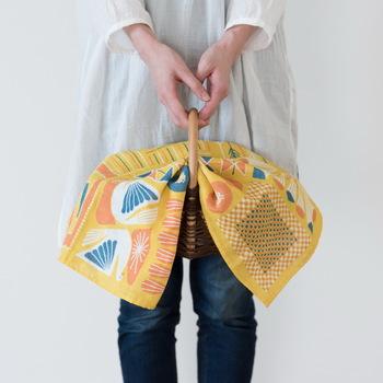 かごやトートバッグの覆いとして布を使うのもお洒落です。埃よけという実用性のほか、その場の雰囲気を明るくしてくれるという効果もあります。畳み方で大きさもアレンジできるので、どのくらいの色味を見せるか調整するのも簡単です。
