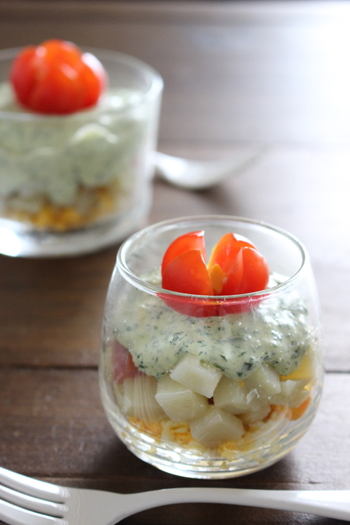 じゃがいもやベーコンなどの材料を耐熱皿に入れて加熱、後はみじん切りにしたパセリとマヨネーズを和えたソースに混ぜるだけの簡単料理。最後に4等分に切ったミニトマトをのせれば、おしゃれな前菜の完成です。