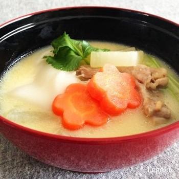 白みそをたっぷりと入れ、とろりとした濃厚な白みそ仕立てのお雑煮はまるでシチューのような味わいです。白いお汁にニンジンや三つ葉の色が鮮やかに映えています。